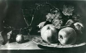 Een stillleven met fruit op een Wan Li-bord en een wijnglas op een tafel