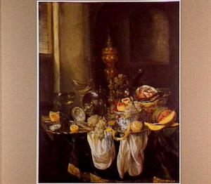 Stilleven met fruit, glas- en zilverwerk, akeleibeker en porseleinen kom en een ham in een mand,  op een donker kleed met wit servet
