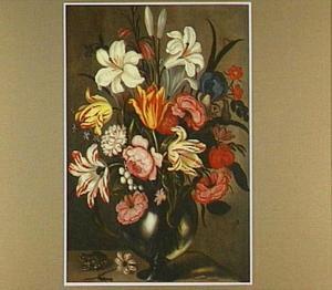 Bloemen in een glazen vaas met een kikker ernaast