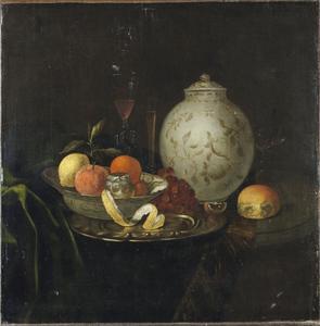 Stilleven met porseleinen vaas en schaal, vruchten en glaswerk op een ronde tafel met donker groen kleed