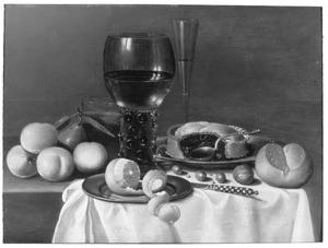 Stilleven met een roemer, broodje, pastei en vruchten
