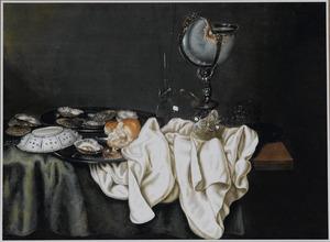 Stilleven met een nautilusbeker, schalen met oesters, een porseleinen schaaltje, een  roemer en ander glaswerk op een deels gedekte tafel