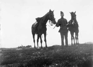 Gezicht op een militair met twee paarden tijdens een militaire manoeuvre