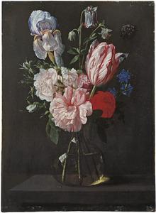Rozen, een tulp, een lis en andere bloemen in een glazen vaas op een stenen plint
