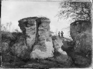 Landschap met steile rotsen, op de achtergrond twee pratende figuren met een hond