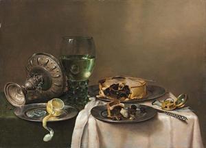 Stilleven met onder meer een omgevallen tazza, een roemer, gebak, en een geschilde citroen op een gedekte tafel