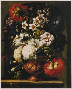 Een urn met een boeket bloemen op een plint voor een stenen nis