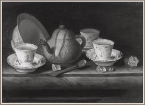 Een Yixing theepot, chinees porseleinen kopjes en een schotel op een marmeren blad