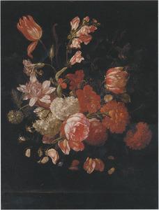 Tulpen, rozen, anjers en andere bloemen in een glazen vaas op een plint