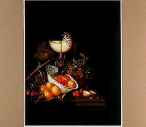 Stilleven met vruchten en een nautilusbeker op een deels gedekte tafel