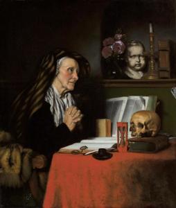 Een oude vrouw biddend aan een tafel