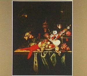 Stilleven van vruchten, bloemen, een kreeft en siervaatwerk op een gedekte tafel en linksboven een papegaai