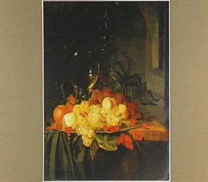 Stilleven met een roemer en vruchten op een schaal op een tafel met een donker kleed