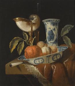 Een stilleven met zuidvruchten,  porselein en een nautilusbeker op een stenen plint met een tafelkleed met franje