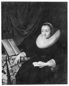Portret van een vrouw zittend aan een tafel met daarop een boek