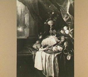 Pronkstilleven met grote ham, vruchten, bekerschroef met roemer en siervaatwerk op een tafel met kleed en wit servet; links een doorkijkje naar tuin
