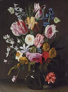 Boeket met rozen, tulpen en andere bloemen in een glazen vaas op een plint