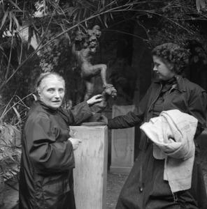 De weduwe van Antoine Bourdelle met Dora Wellensiek bij een werk van Bourdelle in de tuin bij het atelier.