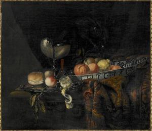 Stilleven met vruchten in een Wan Li-schaal, een nautilusbeker en een oosters tapijt op een tafel