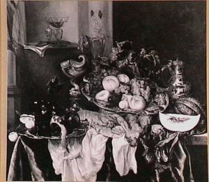 Pronkstilleven met krulbeker, kreeft, sierglas- en vaatwerk, vruchten, porseleinen kan, horloge op een donker kleed met wit servet; een nis met glaswerk en muziekboek