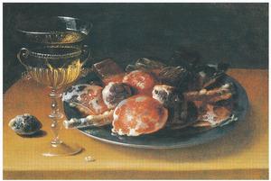 Stilleven met een wijnglas en een tinnen bord met zoet gebak