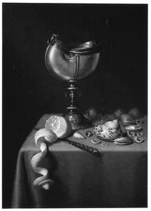 Stilleven met nautilusbeker, geschilde citroen, schelpen en walnoten op een donker kleed