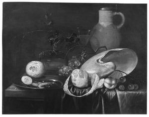 Stilleven met vruchten, garnalen, een kruik, een gepelde citroen en een nautilusschelp op een gedrapeerde tafel