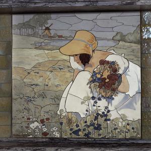 Bloemen plukkende vrouw in landschap met molen