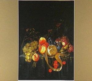 Perziken, kersen en een geschilde citroen op een tinnen schaal, pruimen, hazelnoten, druiven en een Venetiaans wijnglas op een stenen richel, die gedeeltelijk bedekt is door een gedrapeerd groen kleed
