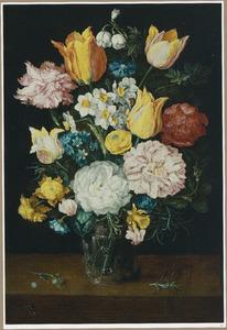 Boeket bloemen in een glazen beker op een houten blad