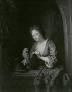 Jonge vrouw in venster, een papegaai voederend
