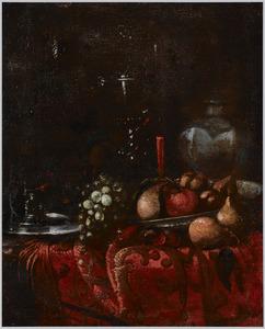 Roemers, een steengoed kruik, een tinnen bord, druiven, peren en ander fruit op een, met een oosters kleed bedekte, tafel