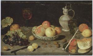 Porseleinen schaal met vruchten, een wijnglas, een roemer, een steengoed kruik, druiven, olijven en noten op een tafel