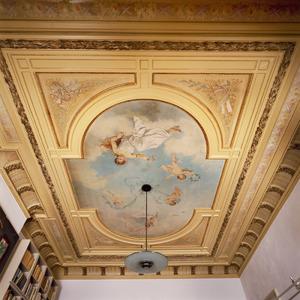 Wolkenlucht met  jonge vrouw en putti omgeven door gestucte en beschilderde ornamenten