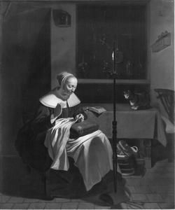 Interieur met handwerkende vrouw bij kaarslicht