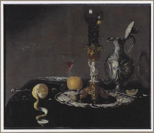 Stilleven met wijnglas, bekerschroef, zilveren kan en vruchten op een tafel