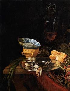 Stilleven met Spaans aardewerk, Chinees porselein, een hoog wijnglas, brood, druiven en een gefillerd visje op een zilveren schaal