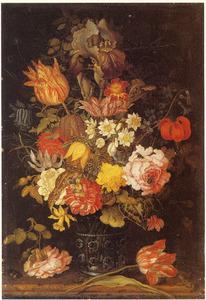 Bloemstilleven in een glazen beker, met een roos, tulp, kever, een rups en een hagedis op een stenen tafel