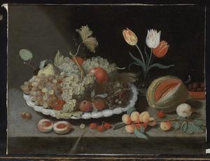 Vruchtenstilleven met een vaasje tulpen op gedekte tafel