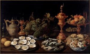 Stilleven met oesters, vruchten, koekjes en siervaatwerk
