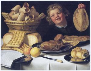 En jongentje met een pannenkoek achter een tafel met gebak, zuidvruchten en een gebraden haan