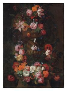 Bloemen in en om een tuinvaas op een stenen sokkel