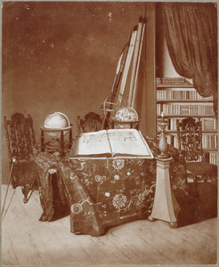 Interieur van een studeerkamer met een openliggende atlas en twee globes