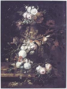 Bloemen in en om een tuinvaas gedrapeerd