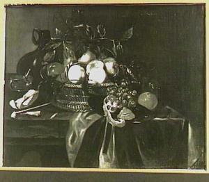 Stilleven met vruchten in mand, serviesgoed, tabak en pijp op een tafel met groen kleed