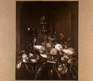 Stilleven met akeleibeker, roemer en porseleinen schaal met vruchten op een donker kleed