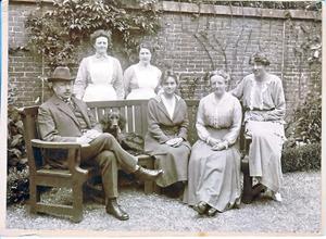 Links en rechts op de bank Gerrit Jan Verburgt (1871-1926) en Lien Verburgt-Kramers (1876-1968) met rechts op de leuning van de bank Annie Bremmer-Hollmann (1895-1989), echtgenote van Floris Bremmer (zoon van Hendricus Petrus Bremmer, 1871-1956); midden op de bank een onbekende; foto genomen in de tuin van het woonhuis aan de Koninginnegracht 44, Den Haag