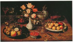 Stilleven met nautilusbeker, boeketje bloemen in porseleinen vaas en schotels met vruchten