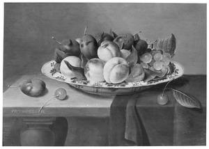 Stilleven van een porseleinen schaal met vruchten op een deels met een donker kleed gedekte tafel