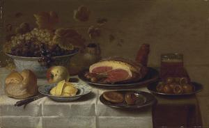 Stilleven met druiven, een appel, ham, mispels, boter en brood op een gedekte tafel